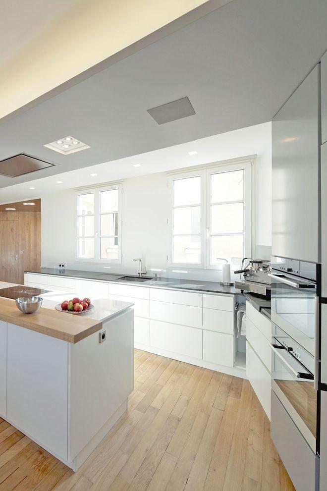 Une cuisine blanche baignée de lumière et ouverte sur la salle à