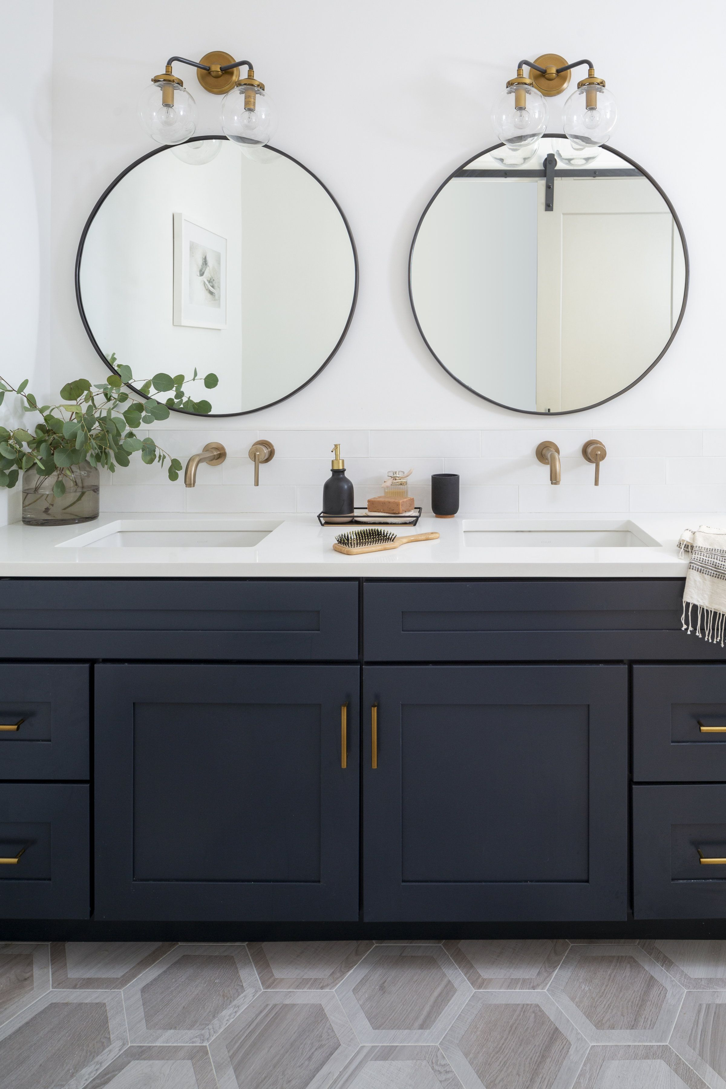 Photo of Navy double vanity bathroom with brass fixtures and round mirrors. Hexagon tile …