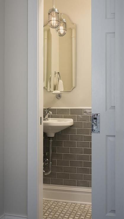 A Pocket Door Opens To Small Gray Powder Room With Light Paint On Upper Walls And Charcoal Subway Tiles Lower Lined Curved