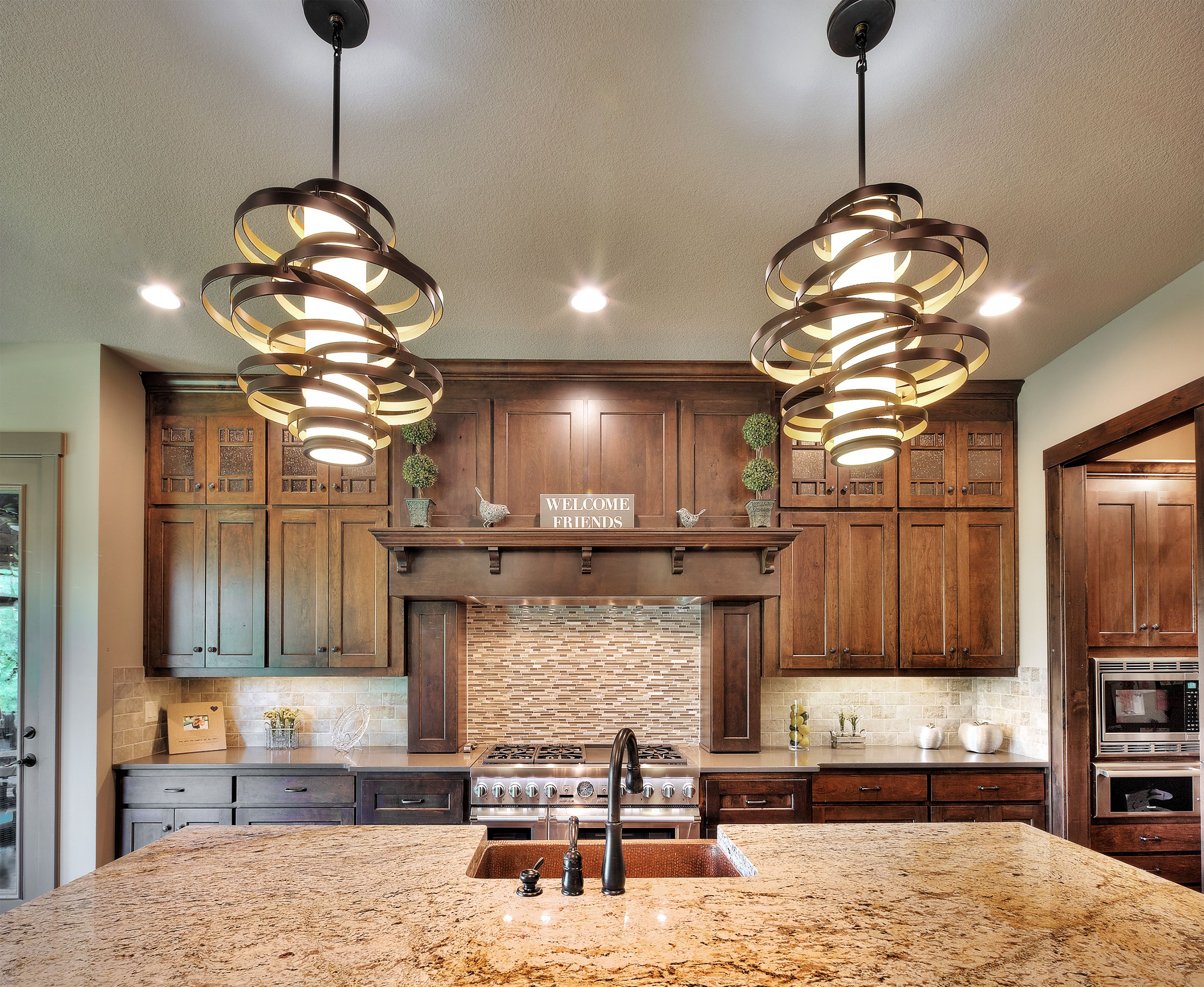 Warm wood cabinets in kitchen with light fixtures over ...