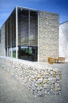 Edificio con fachada de gaviones de piedra detail for Gaviones de piedra