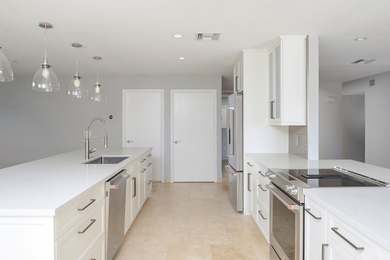 Contemporary, galley style, white kitchen with a window pass through ...