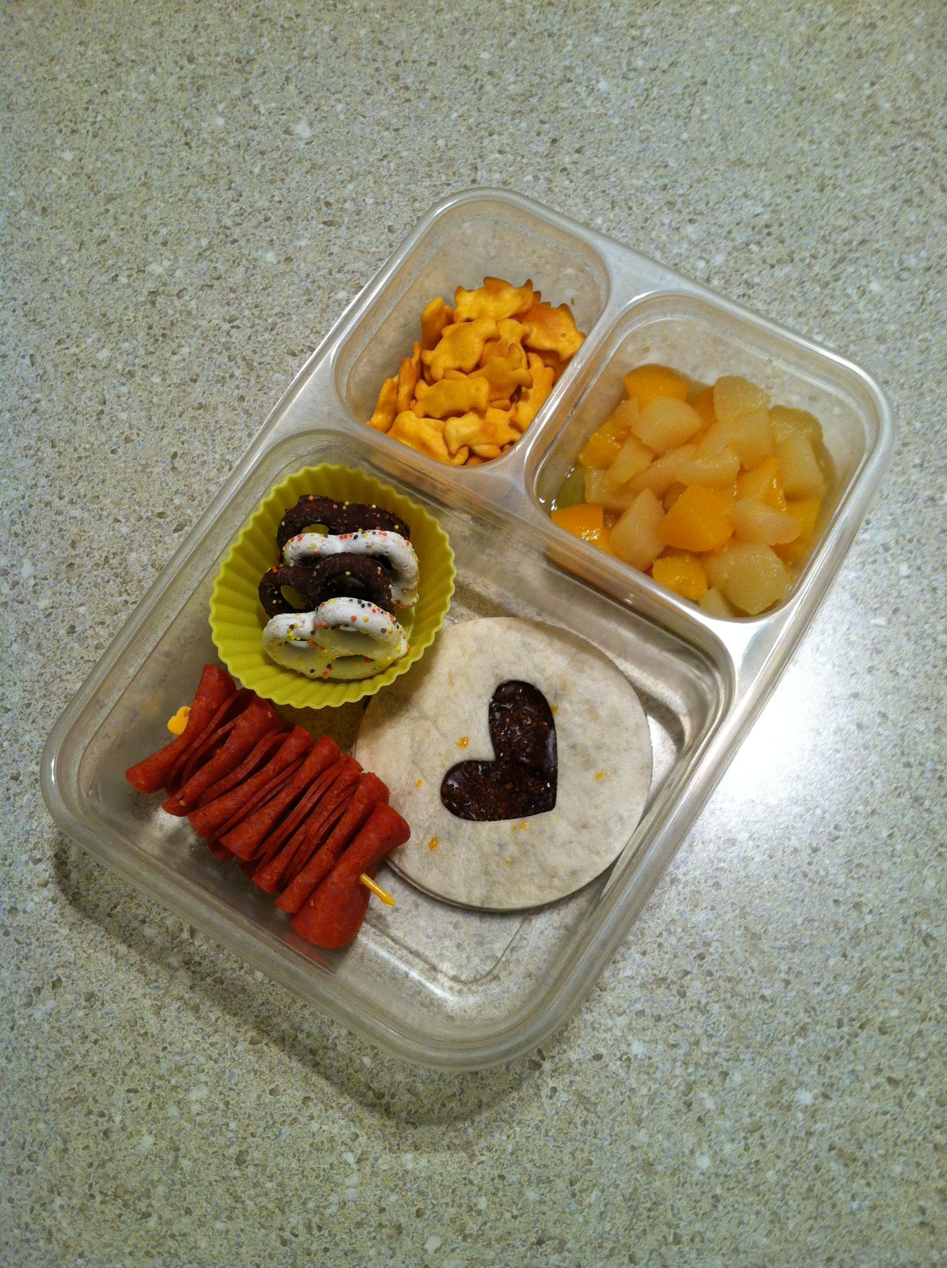 Bento lunch w Nutella tortilla, turkey pepperoni, chocolate pretzels, cheese penguin crackers & fruit