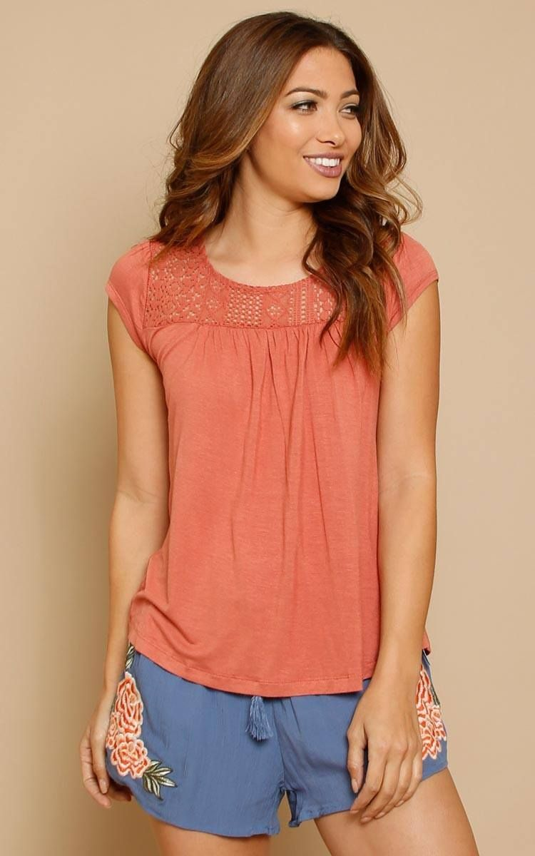 87ebcc55ed Short sleeve knit top featuring a high socoped neckline with floral crochet  inset. Crochet back with lace up accent and split back detail.