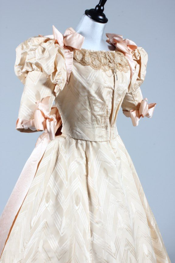Ivory damask ball/bridal gown, circa 1895, the bodice with puffed upper sleeves adorned with pink satin ribbons, matching skirt with chevron and ellipse repeats