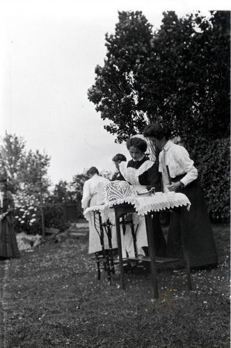Jane at work serving tea in the garden at 'Faussethill' on 30 July 1912. Jenny Cameron has stopped playing golf to supervise the operations. The richly decorated tea cosy is probably keeping warm a silver tea pot, its matching sugar bowl can be clearly seen on the oblong table. This photograph is held in Glasgow University Archive Services. For more information please contact the Duty Archivist: www.gla.ac.uk/services/archives/contactus/ (Reference number: DC111&...