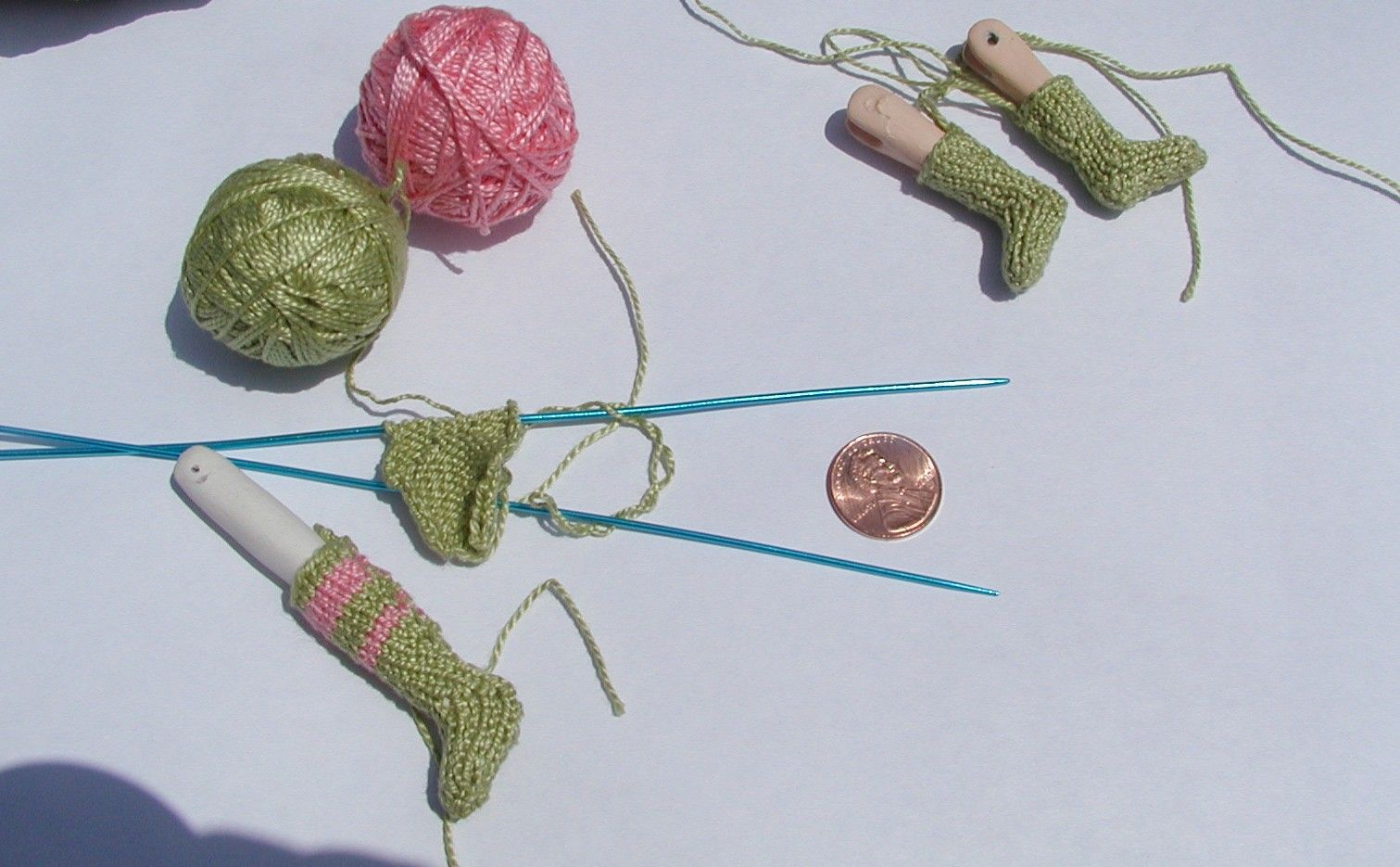 I did learn how to knit socks for my miniature (dollhouse) dolls... and they're my first attempt, so I'm really, really proud of them... I included a penny so you could see how small (and thus even cuter) they are <3