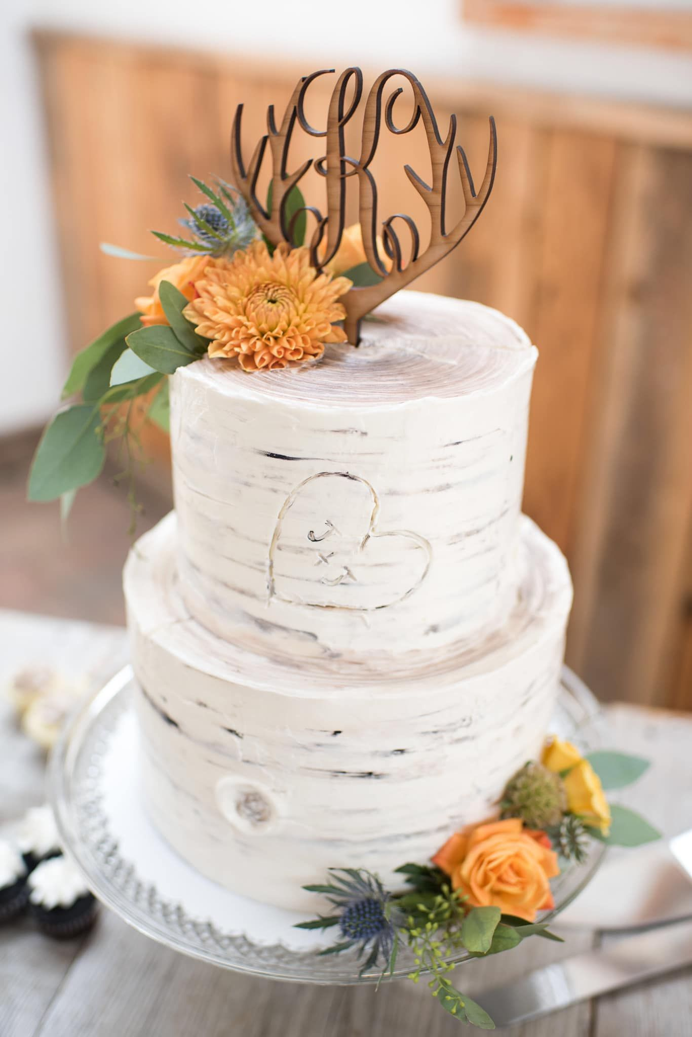 Two Tier Birch Bark Wedding Cake With Custom Wood Topper And Fresh Yellow Orange And Blue Thistle Flowers Creative Wedding Cakes Wedding Cakes Tiered Cakes