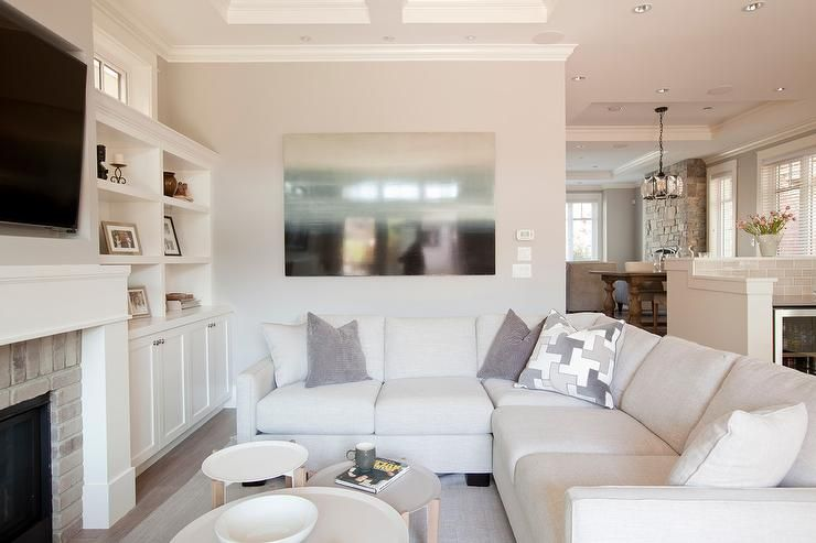 Remarkable An Off White Linen Sectional Topped With Gray Pillows Sits Gmtry Best Dining Table And Chair Ideas Images Gmtryco