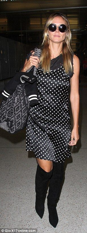 The terminal is her runway! The former Victoria's Secret Angel, 43, strutted through the busy airport in a black and white polka dotted frock and over-the-knee black suede boots