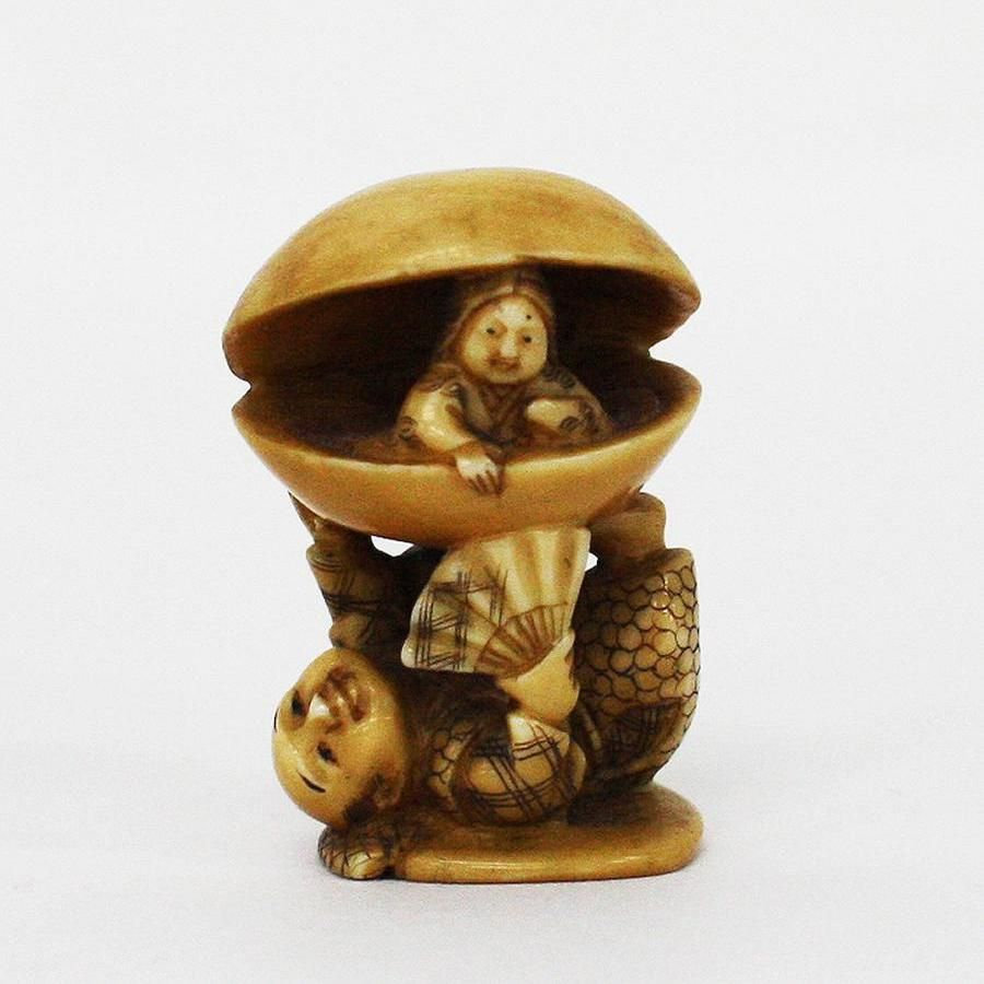 ♥ Early 20th century Japanese ivory netsuke carved depicting a man lying on his back, holding up a clam shell on his feet with a lady inside. ...