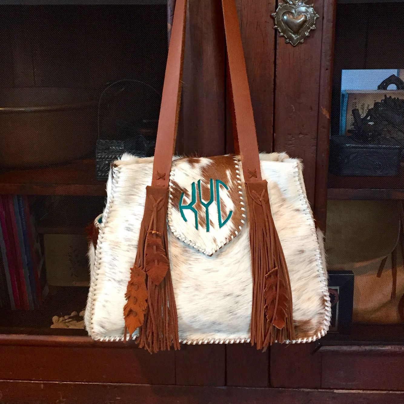 An off-white cowhide Bonnie Bag with the customer's circle monogram in turquoise suede, and deerskin feathers on the fringe. From gowestdesigns.us