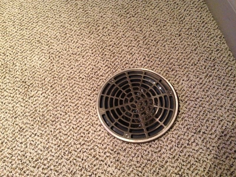 Close-up of floor drain cover over carpet. | Basement project