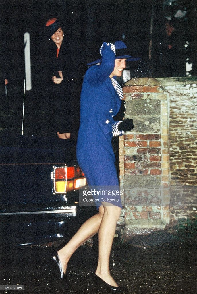 December 25, 1990: Diana, Princess of Wales, clutches her hat on the way to Sandringham Church for Christmas Day Service in Sandringham, England.