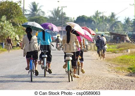 Women with umbrellas riding bicycles.