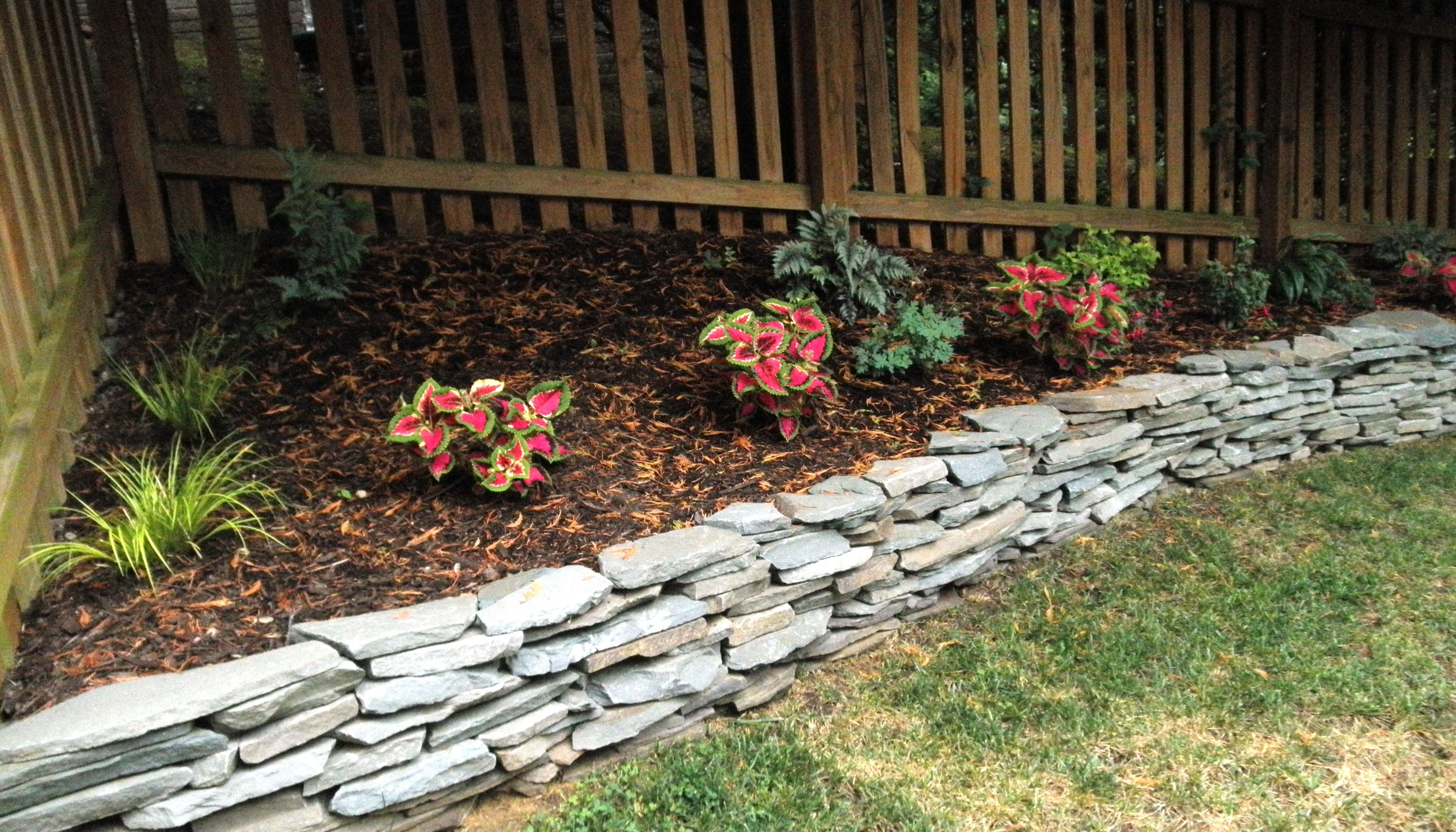 Stacked stone raised flower bed. I hope it helps to prevent erosion ...