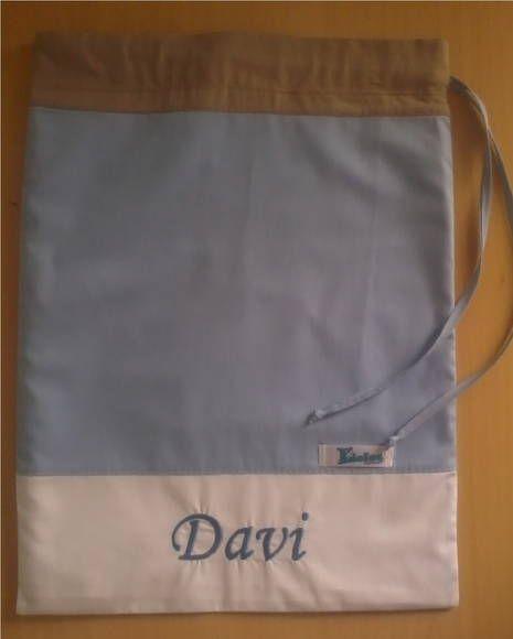 Confeccionado em tecido 100% algodão, forro interno em plástico branco, cordão em tecido para o fechamento e bordado à máquina. R$ 25,90