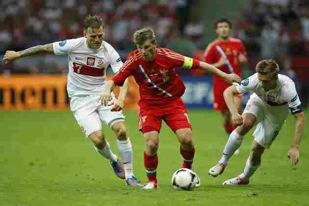 Poland 1 Russia 1 in 2012 in Warsaw. Andriy Arshavin cuts in between 2 Polish defenders in Group A at Euro 2012.