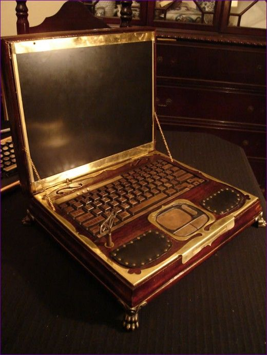 """Steampunk Laptop! The machine turns on with an antique clock-winding key by way of a custom-built ratcheting switch made from old clock parts. The violin-style sound holes, or """"F-holes"""" are functional speaker grills covered with black cloth. The original keyboard LEDs now shine through small plastic gems.""""   from - Datamancer.net"""