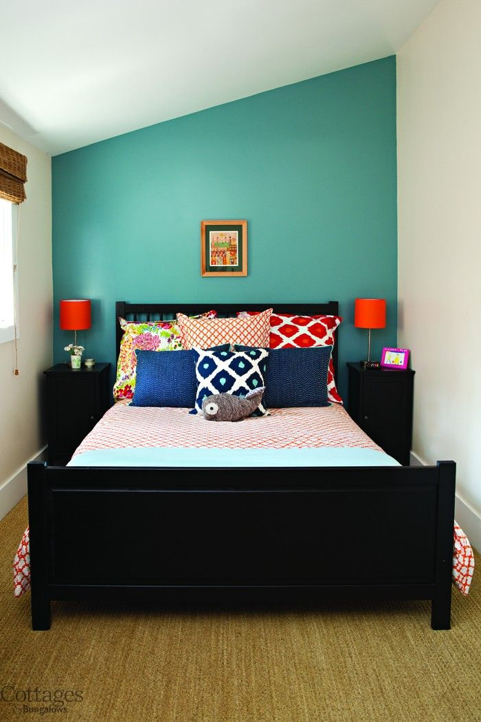 small cottage guest bedroom with lots of bright accents pillows and accent wall