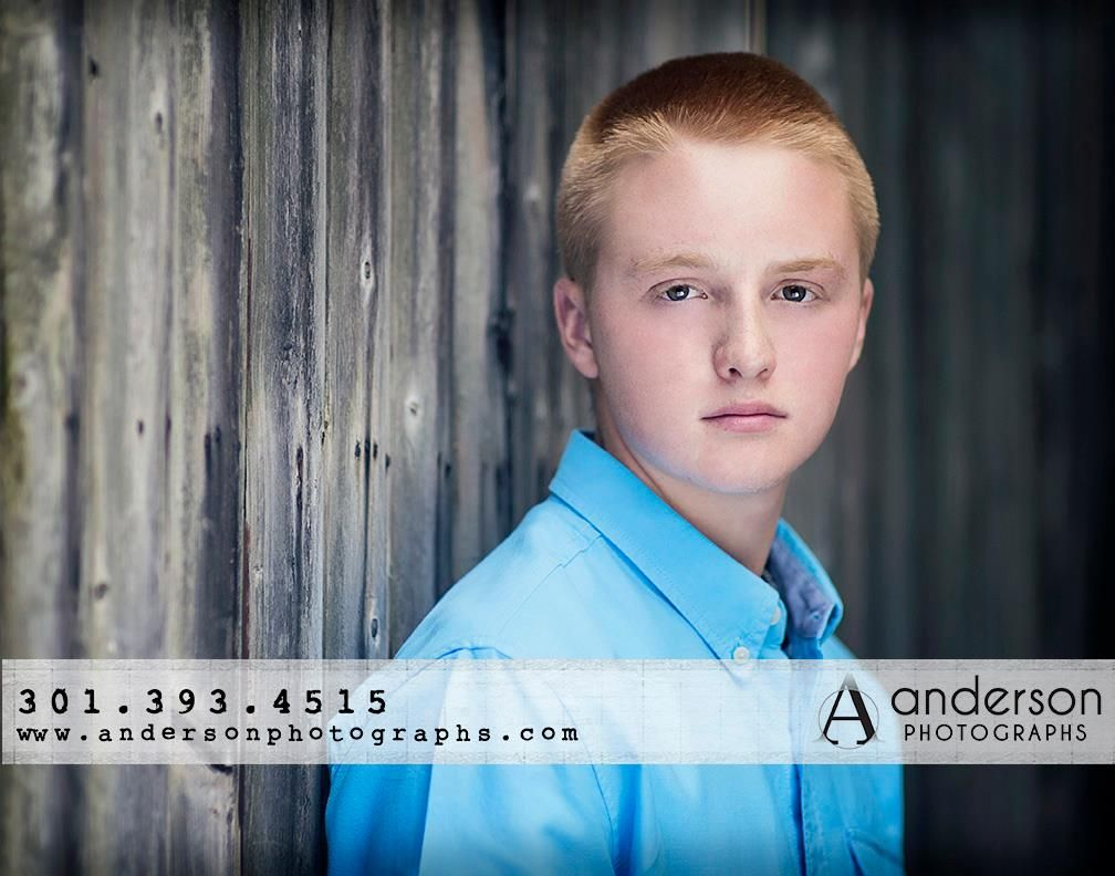 Senior boy in blue during a senior session with Anderson Photographs. Location fence row www.andersonphotographs.com
