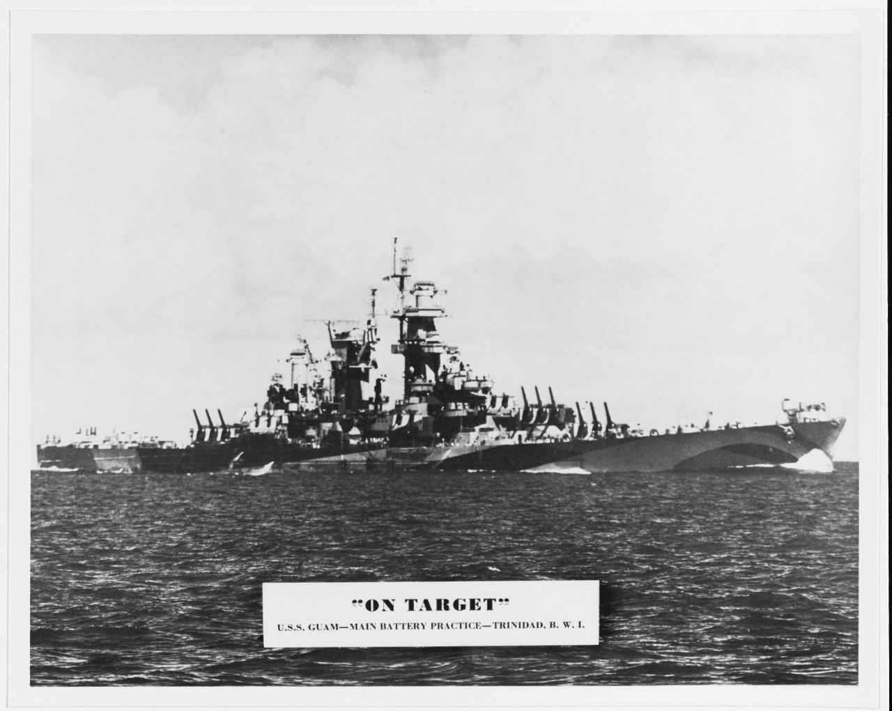 """""""USS Guam (CB-2). Halftone photo of the ship conducting main battery gunnery practice during shakedown off Trinidad, November-December 1944. Copied from the ship's wartime cruise book, U.S.S. Guam: Her Story, 1944-1945. U.S. Naval History and Heritage Command Photograph."""" (NHHC: NH 90736)"""