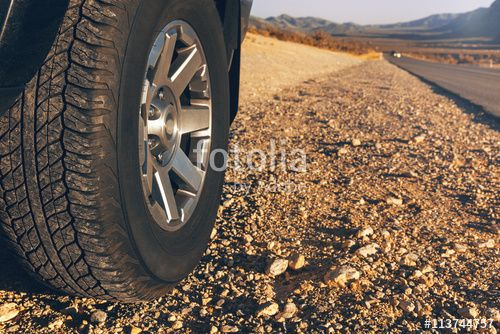 Car tire on dirt road at sunset time