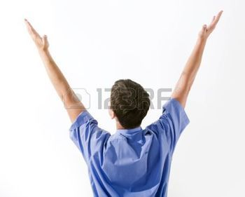 glory: Rear view of man in blue shirt keeping his arms raised over white background Stock Photo
