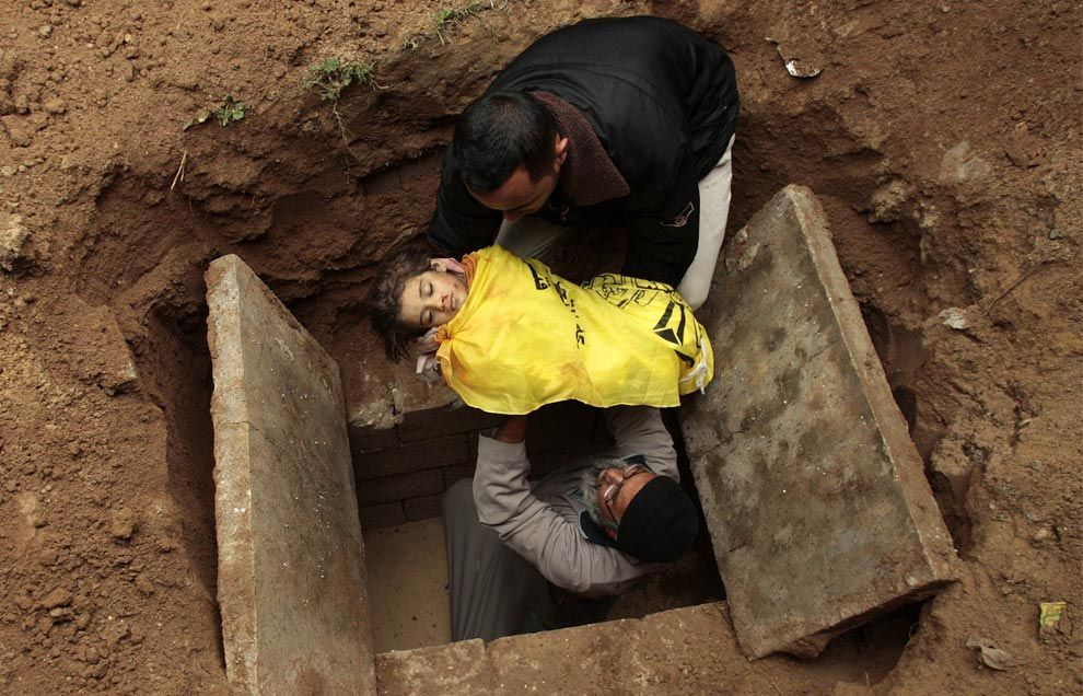 Palestinian men bury the body of 4-year-old Lama Hamdan at Beit Hanoun cemetery in the northern Gaza Strip December 30, 2008. Lama and her sister were reportedly riding a donkey cart Tuesday near a rocket-launching site that was targeted by Israel
