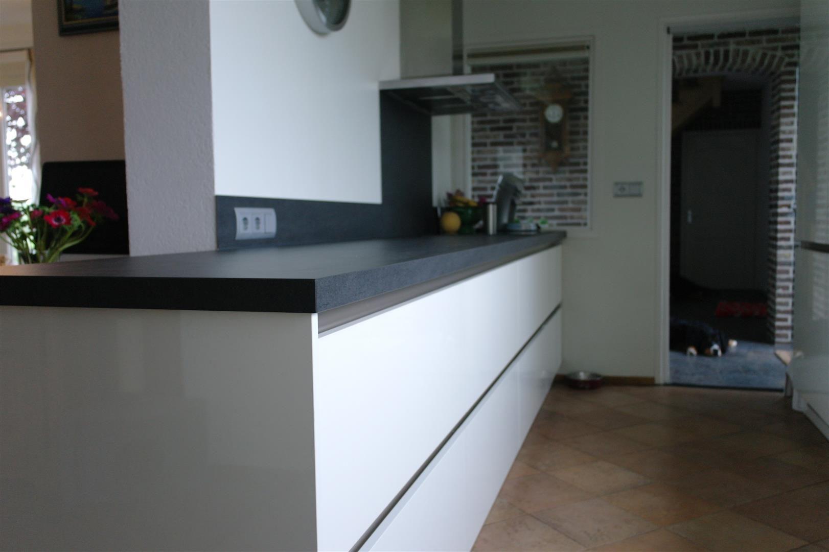 Strakke greeploze hoogglans witte keller keuken met keramiek