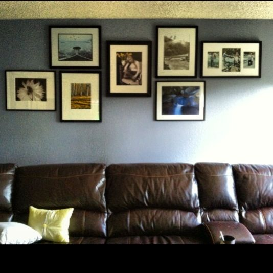 Photo Mural With Various Black Frames On A Light Blue Wall With Brown Leather Couch Planning To Have Mul Light Blue Walls Living Room Lighting Apartment Decor
