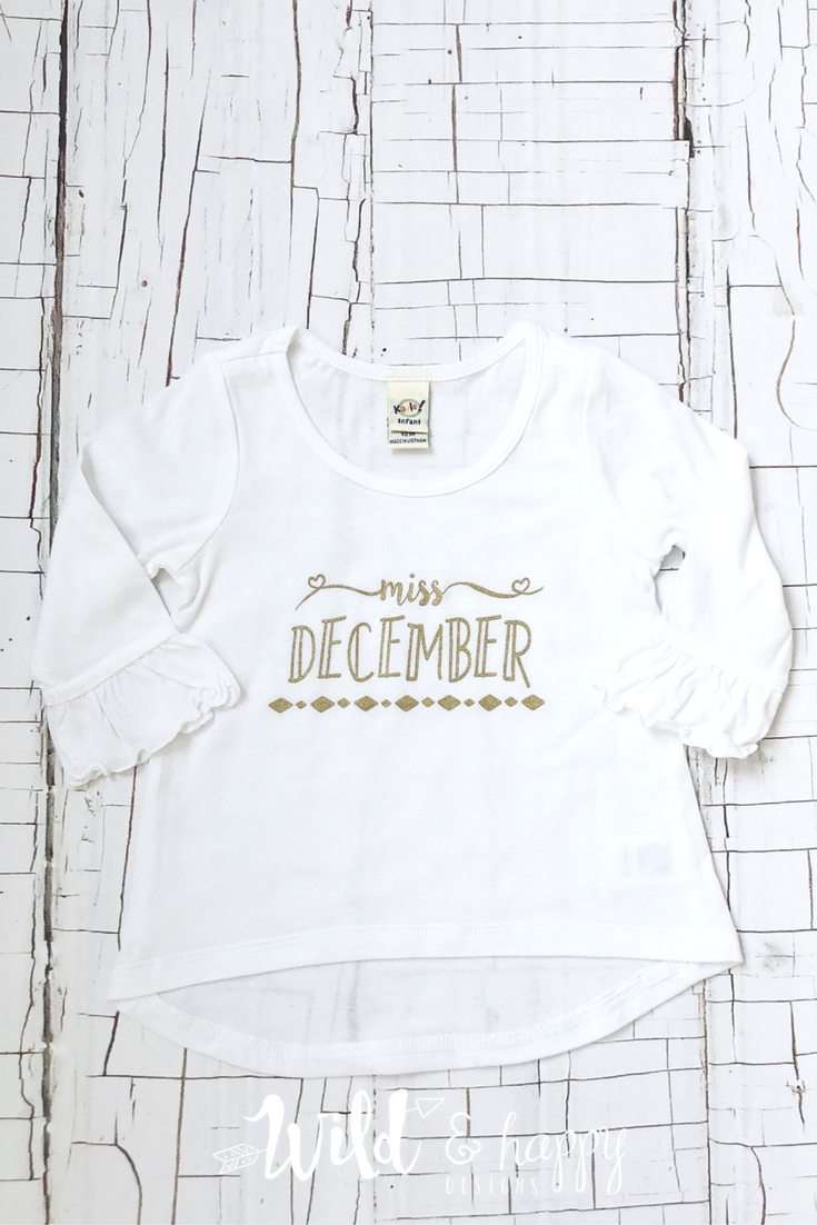 c8be02cd4 Miss December shirt-printed on a ruffled sleeve jersey with gold in that  allows your little girl to rock her birthday month in style!