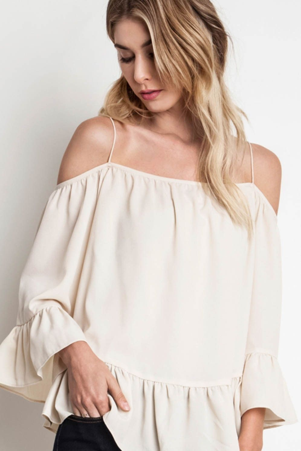 13040f1662b3a Sweet ruffle woven top crafted from a lightweight fabric featuring  spaghetti straps and trumpet sleeve hems. Content + Care  100% Rayon Hand  Wash