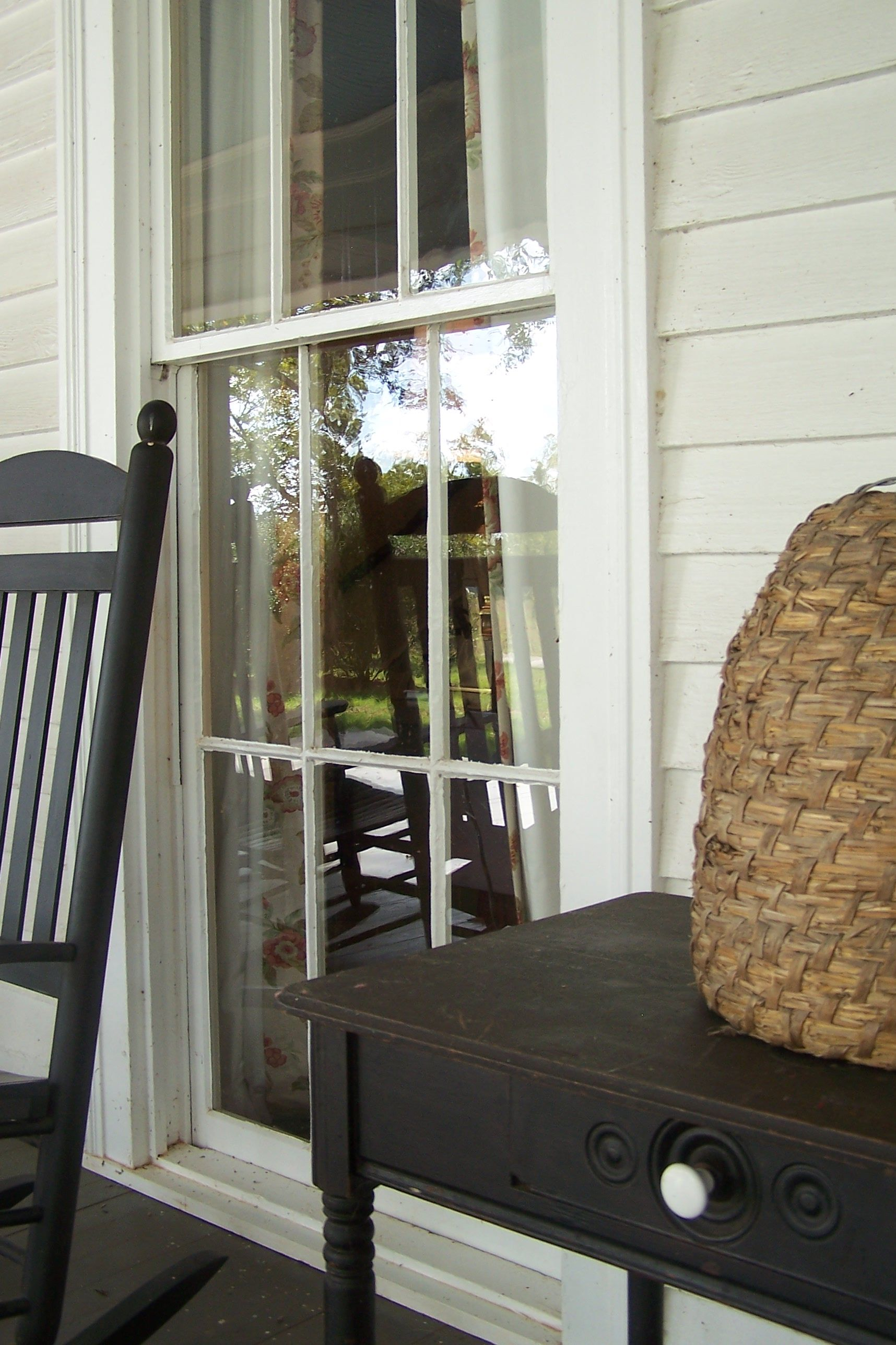 client porch, rocking chair, black, table, bee skep, painted wood floor, view into window, white house
