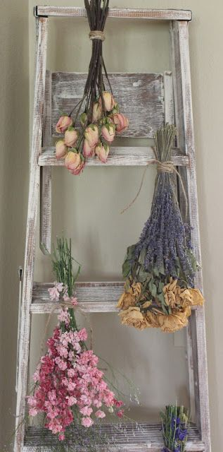 Eine Alte Holzleiter Mit Kalk Farbe In Weiß Gestrichen Und Mit Getrockneten  Blumensträußen Dekoriert.