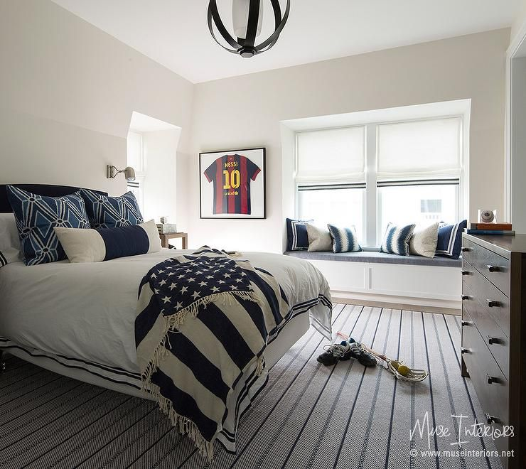 Grown up boy's bedroom features a black curved headboard ...
