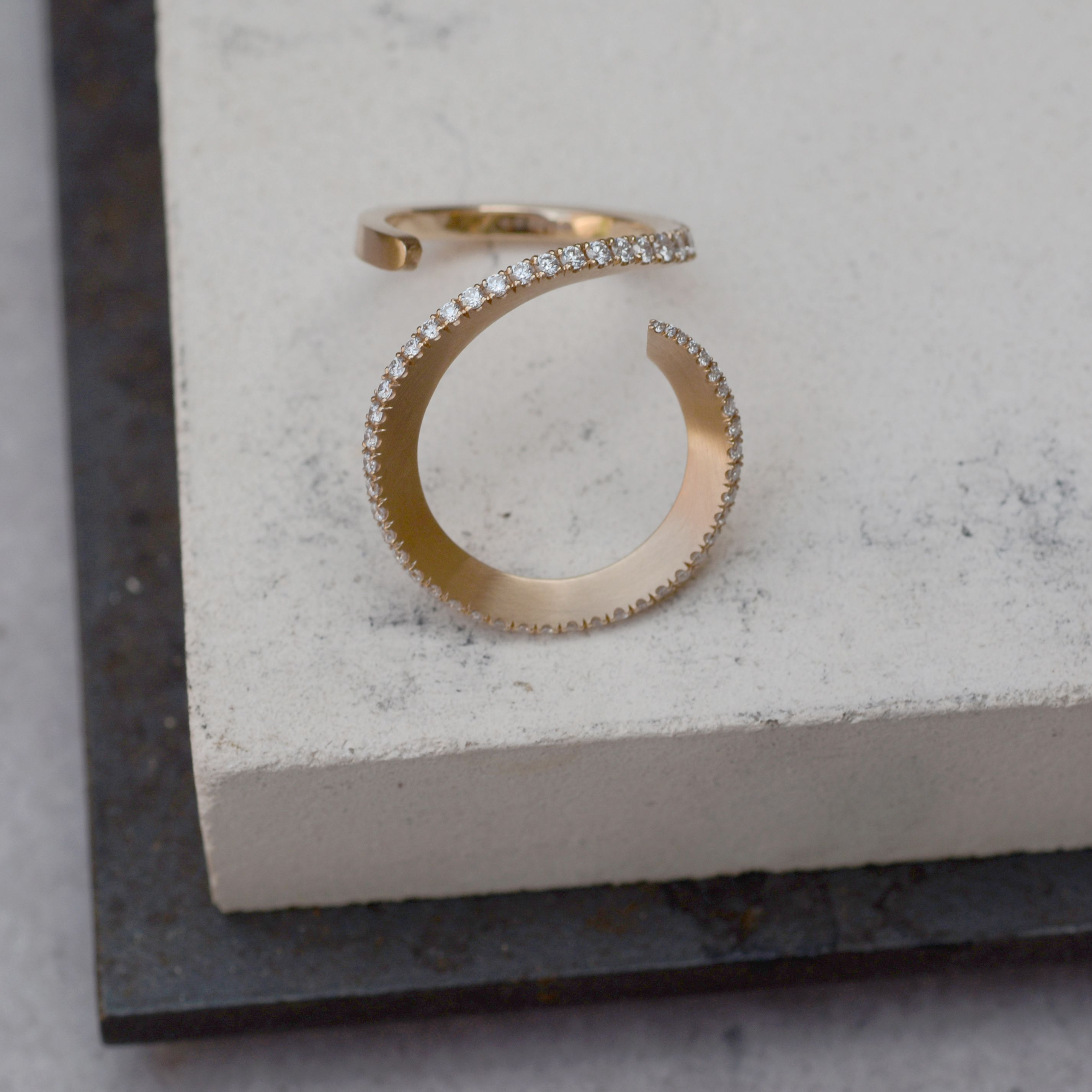The deep circular curve of this unique rose gold and diamond cocktail ring is hand forged from 18ct gold bar and accentuated with a sparkling line of tapering pave white diamonds 💎 Available through our website for click & collect or worldwide shipping. #statementring #cocktailring #handcraftedjewellery #jewellerydesign #jewellerylondon #contemporaryjewellery #shopindependant #craftsmanship #designermaker #bespokejewellery #rosegoldring #diamondring #paveset