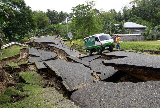 A vehicle transporting a body of an earthquake victim tries to pass through a destroyed road in La Libertad, Negros Oriental in central Philippines