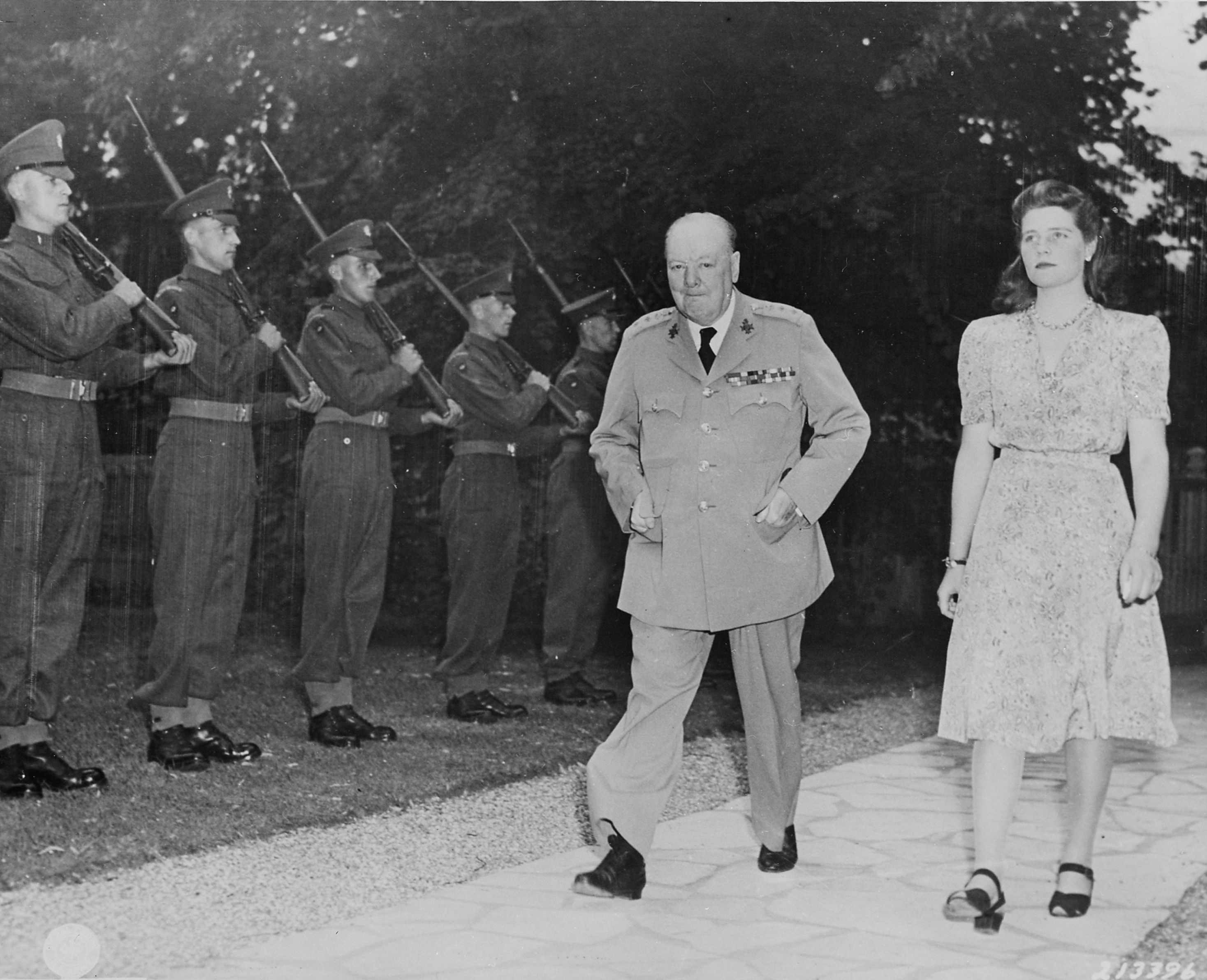 British Prime Minister Winston Churchill and his daughter Mary Churchill walking in the garden of their residence during the Potsdam Conference, Germany, 23 Jul 1945; note British Scots Guards regiment honor guard. Source - United States National Archives