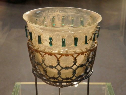 """The so-called Trivulzio Diatreta Cup, a 4th century CE luxury glass cup consisting of an inner beaker and an outer cage of decoration with circular geometrical patterns. Around the surface runs an inscription in Latin """"BIVE VIVAS MULTIS ANNI"""": """"Drink and live many years"""". (Civico museo archeologico di Milano)"""