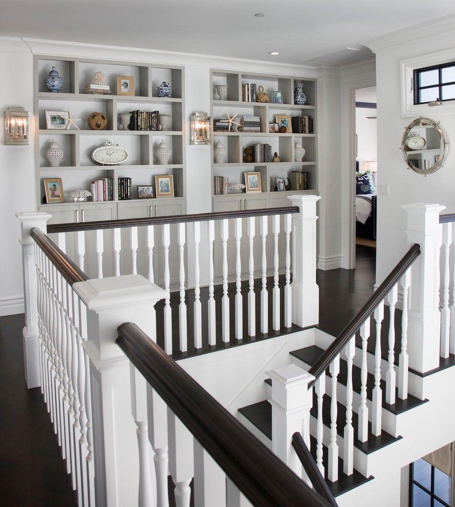 gorgeous coastal stairway with dark wood floors and white pillars
