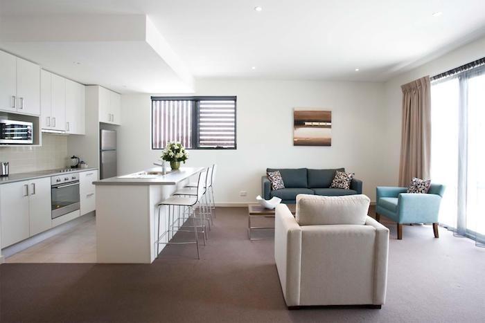 Offene Küche mit Wohnzimmer weiße Küche und bunte Sessel, beige ...