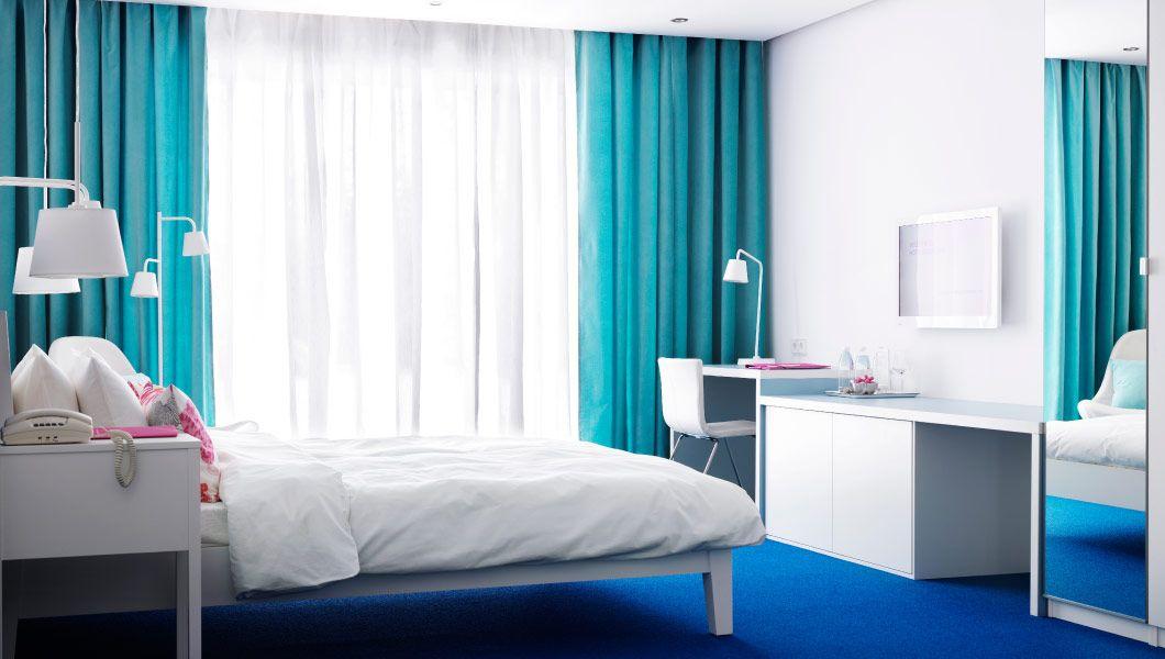 habitacin de hotel con muebles blancos y cortinas turquesa
