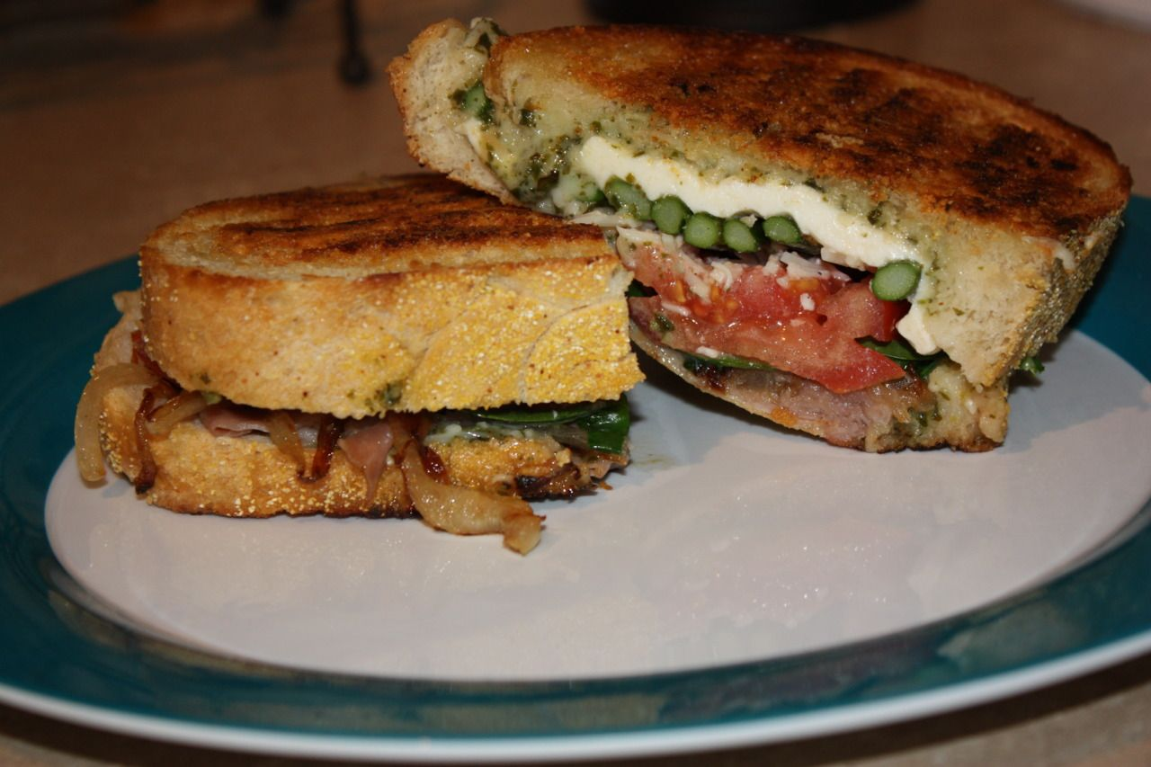 Ultimate panino!  Sourdough bread, pesto, fresh mozzarella, tomatoes, spinach, roasted asparagus, parmesan, caramelized onions, and (I splurged!) prosciutto!!!  Grilled and pressed in a non-stick skillet with a little olive oil.