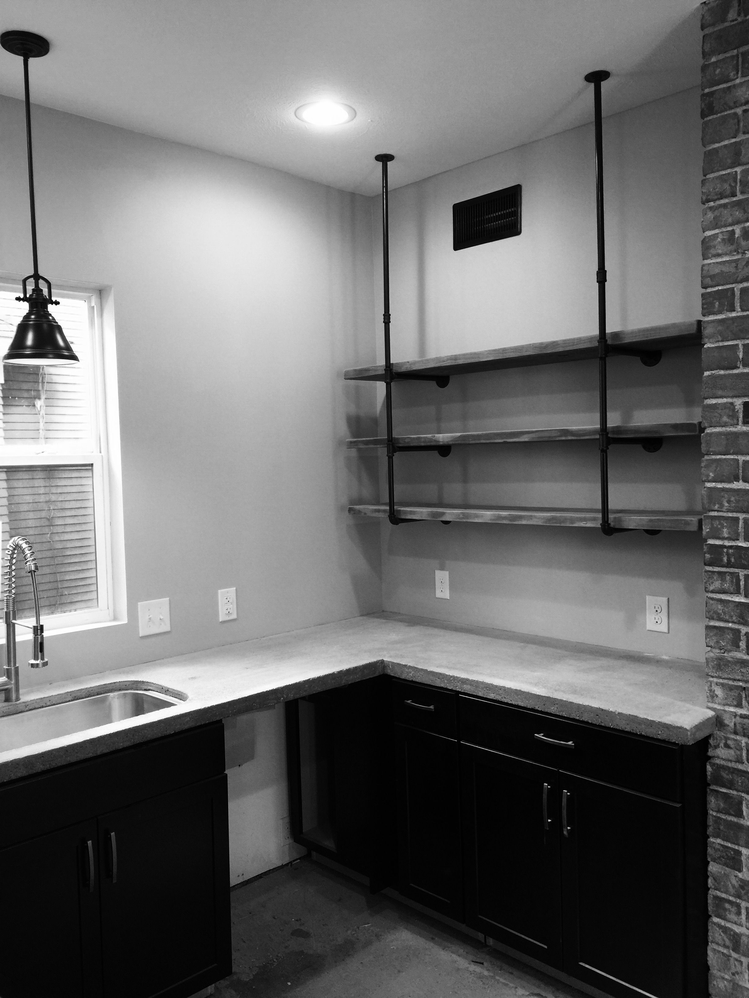 Industrial kitchen concrete counters exposed brick for Black industrial kitchen