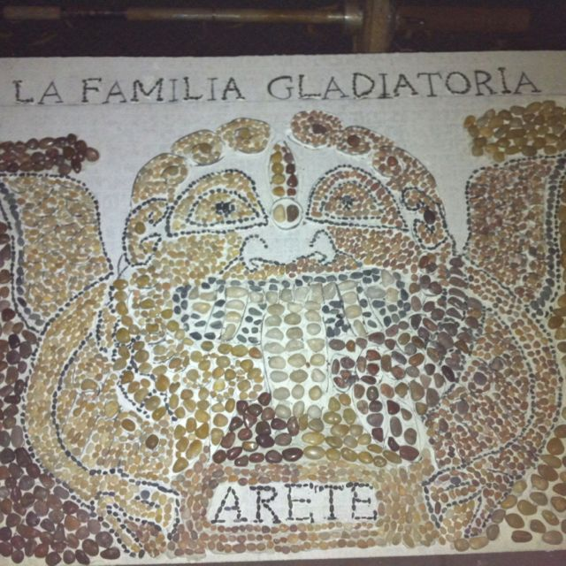 Gorgon, Day 10.5  I think I may leave the rest of the face open and not put pebbles there.  I will be filling in the space between the letters at the bottom but I want to give the thinset a chance to dry first.     Doing the lettering is a little tedious because I want people to actually be able to read it, so I spent a lot of time placing pebbles, looking at them, asking my friends to look at them before continuing.