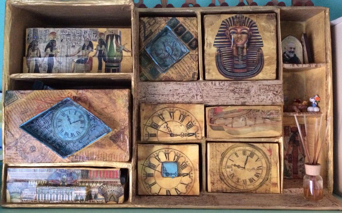 Cassettiera di scatoli ricoperti con carta di giornale e decorata con decoupage