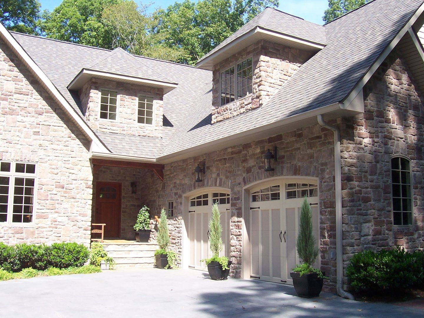 custom stone house with arched garage doors oversized dormers 1212 pitch designed by kerrin muller of muller design company interior and exte - Custom Home Design Company