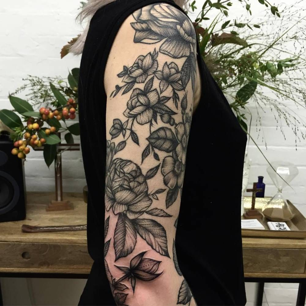 Blackwork style floral tattoo on the right upper arm