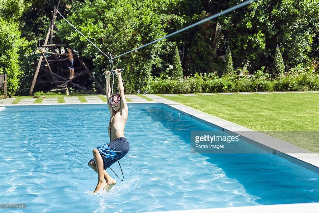 Full length of boy hanging from zip line over swimming pool | Pools ...